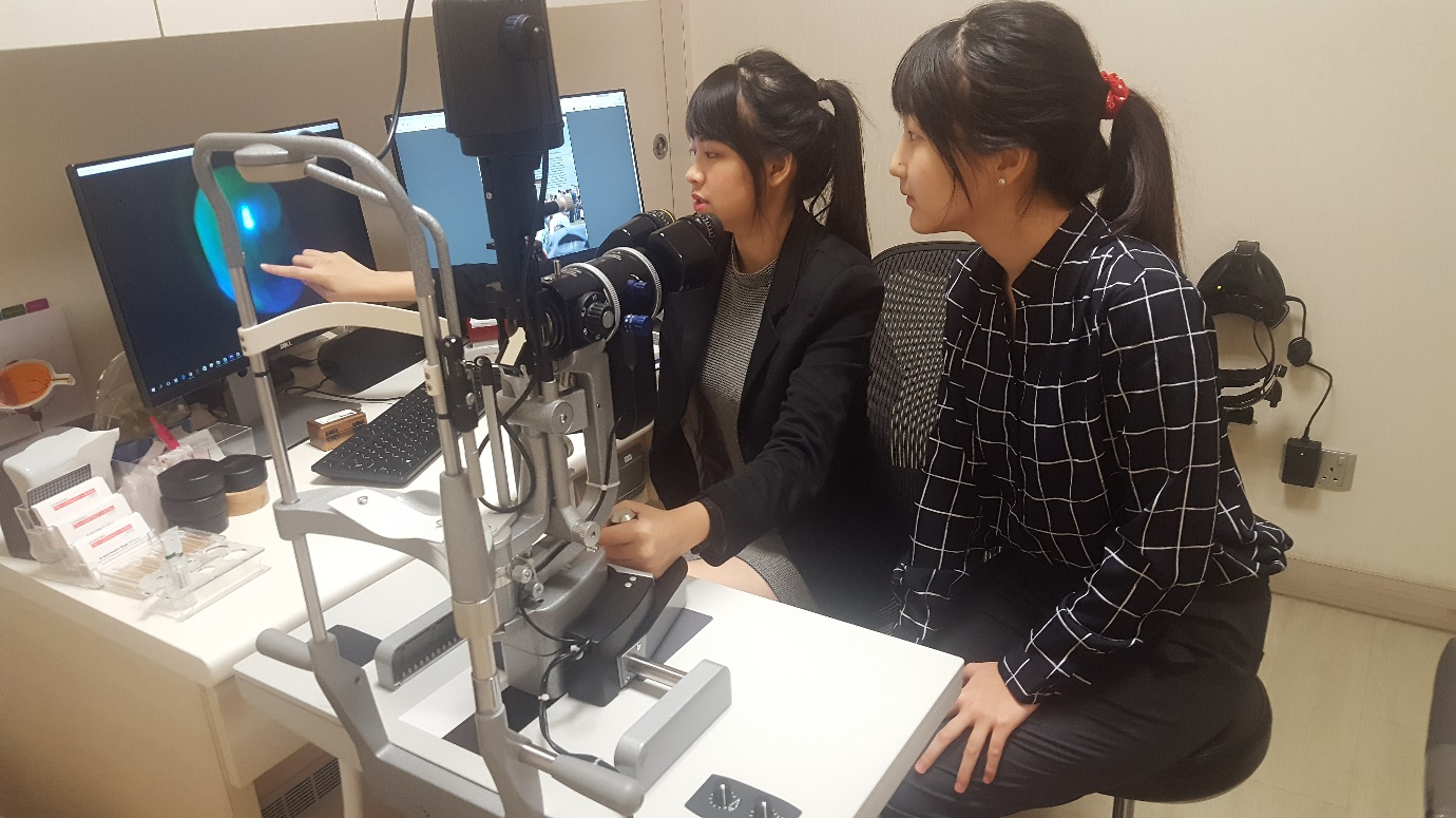Optometrist Goh Jiah Ying (left) showing how a dye called fluorescein sodium is used to examine the surface of the cornea to Raffles Institution student Sophia Kim.