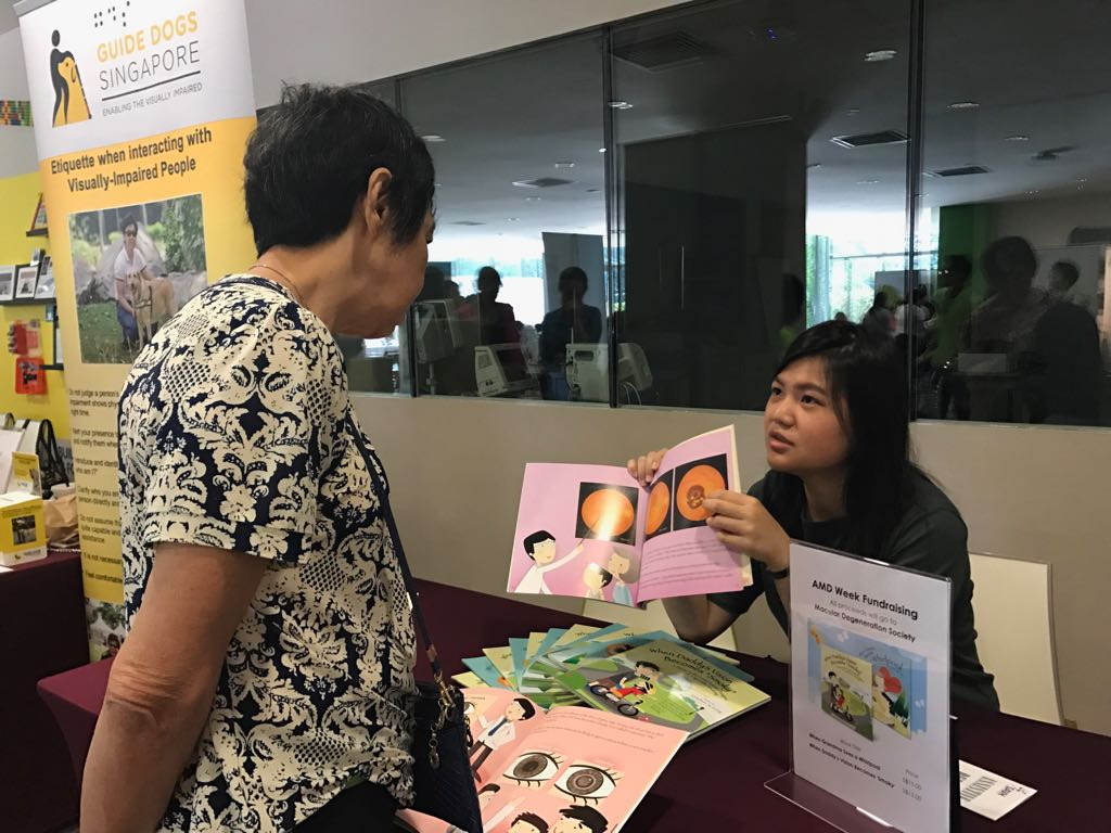 Optometrist Olga Aprianti Lee explaining one of the books for sale to a member of the public.