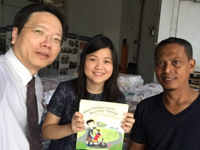 (L-R) Dr Au Eong Kah Guan, Optometrist Olga Aprianti Lee and Mr Fuad from the Ministry of Education's warehouse during delivery of the donated books.