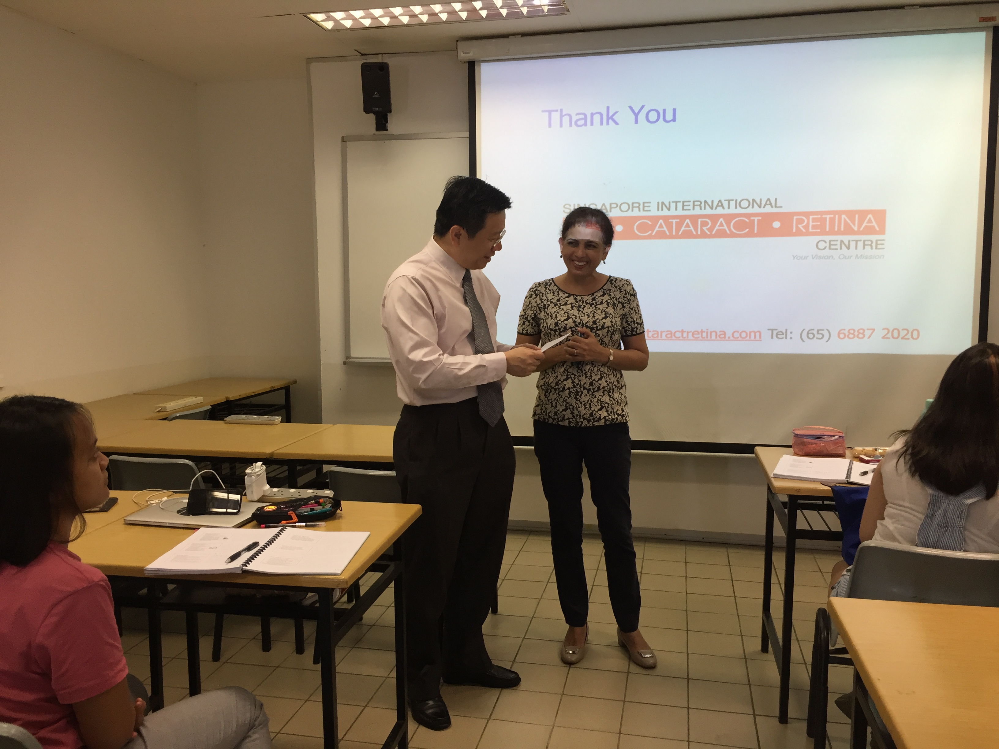 "Ms Sukhdev Kaur (right), Senior Lecturer cum Senior Manager of the Advanced Diploma in Perioperative Nursing course in the School of Health Sciences at Ngee Ann Polytechnic,  presenting a ""thank you card"" made by the students to Dr Au Eong Kah Guan at the end of his lecture."