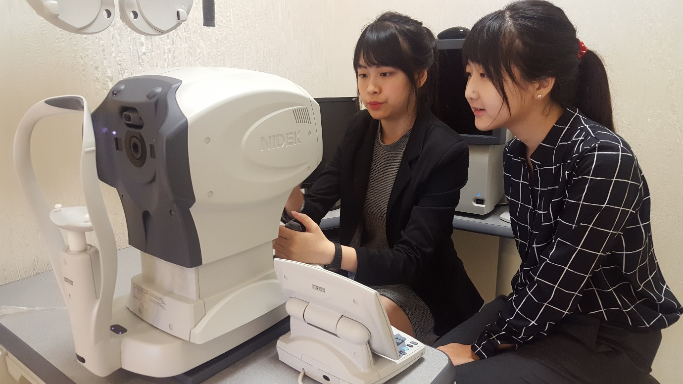 Optometrist Goh Jiah Ying (left) demonstrating the functions of a combined autorefractor, autokeratometer and air-puff tonometer to Raffles Institution student Sophia Kim.