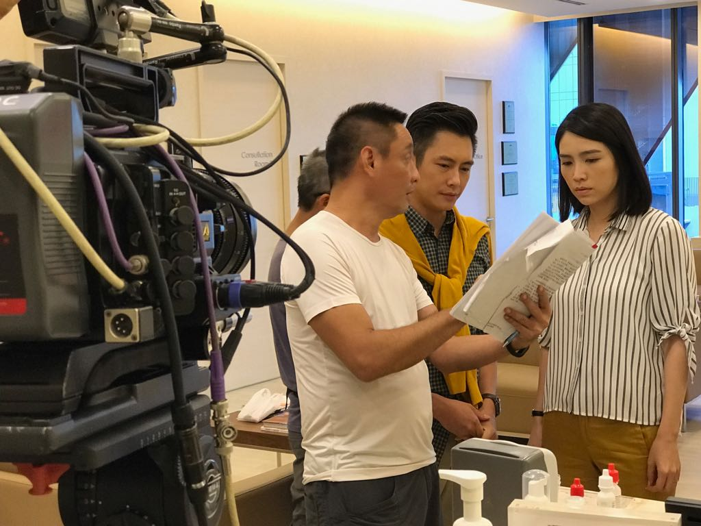 (L-R) Director Lin Mingzhe discussing a scene with actor Zen Chong and actress Sora Ma during a shoot in International Eye Cataract Retina Centre in Farrer Park Hospital.