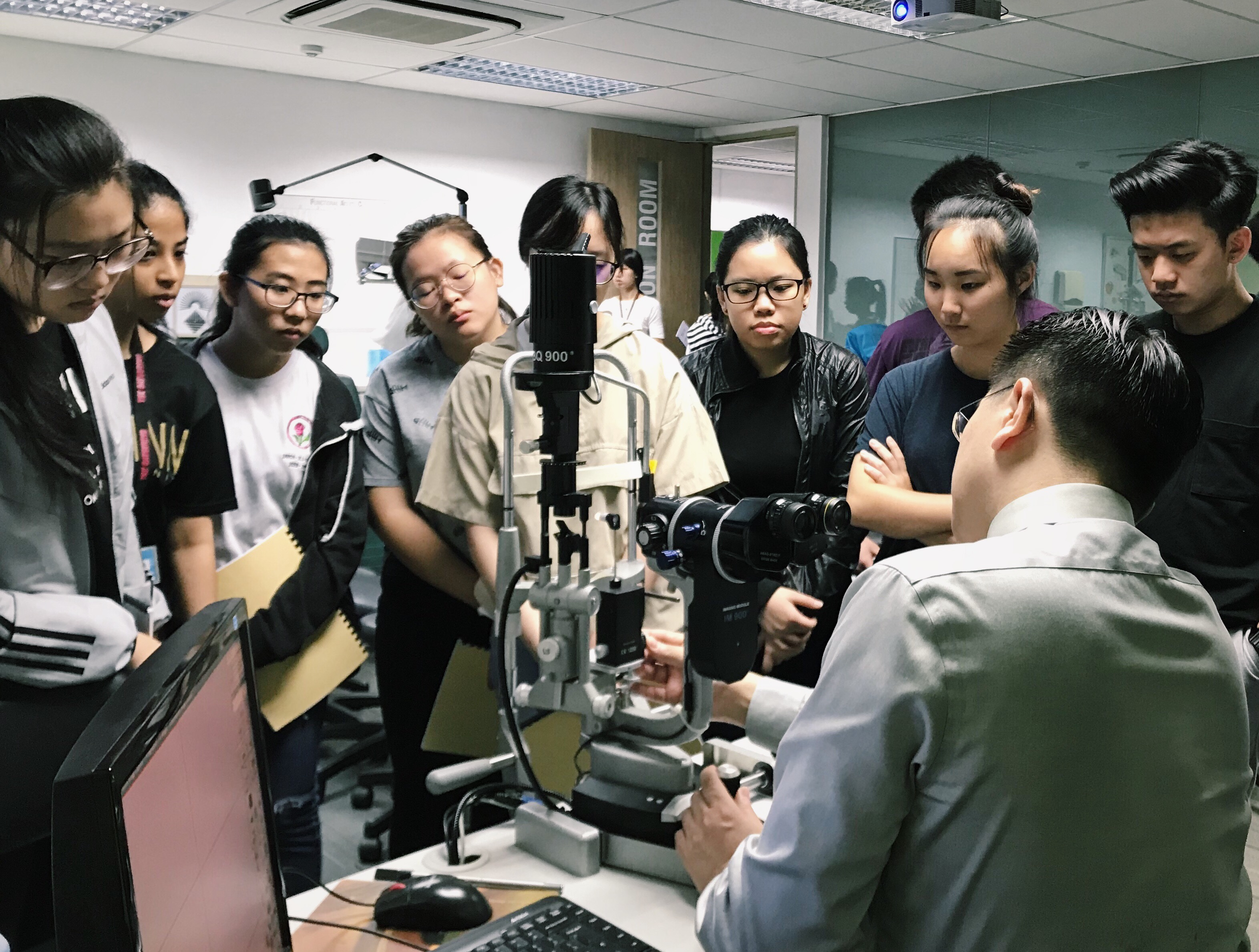 Dr Au Eong Kah Guan (seated) explaining the use of Goldmann applanation tonometer to first year optometry students at Ngee Ann Polytechnic.
