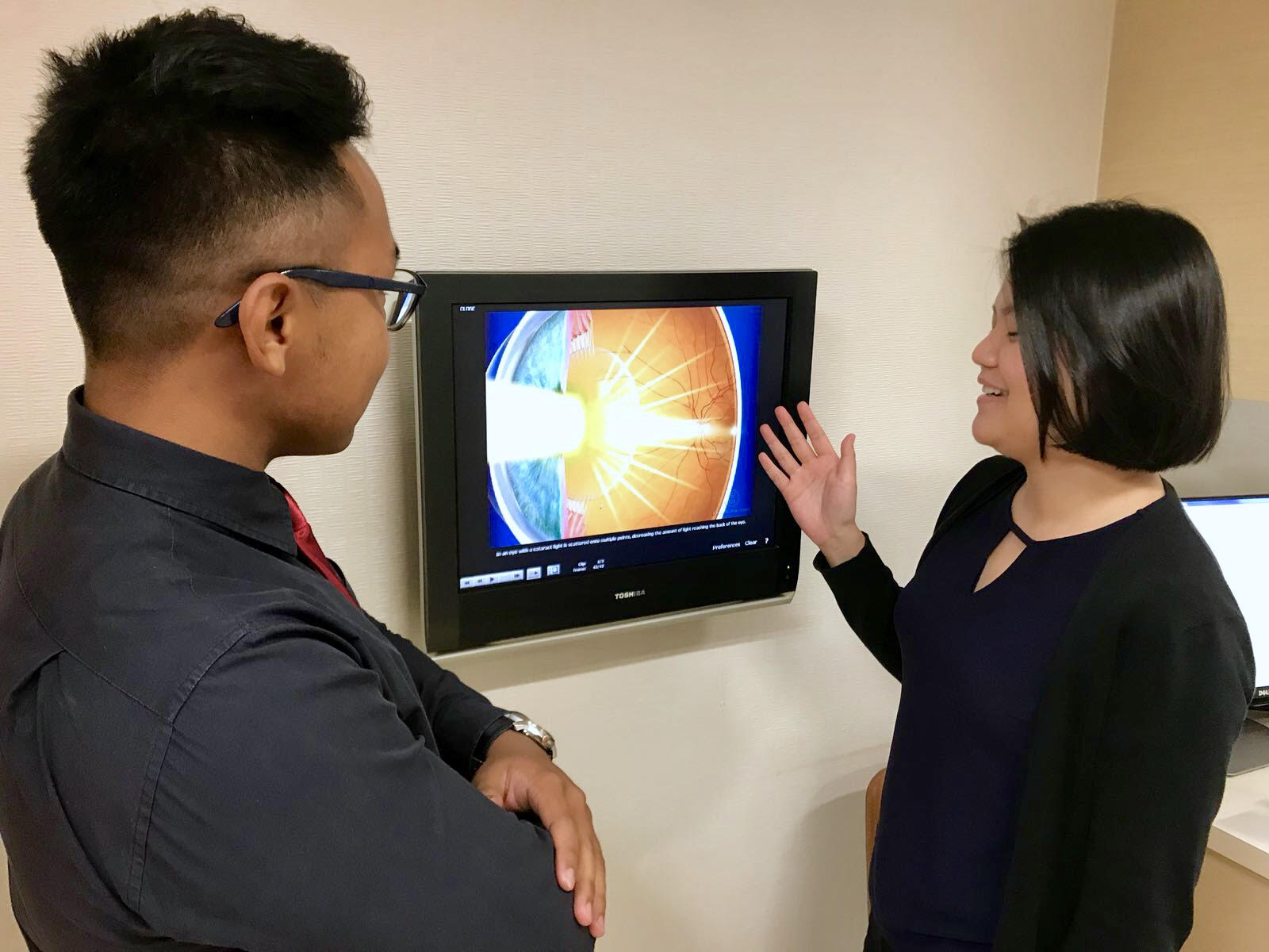 Optometrist and clinic manager Olga Aprianti Lee (right eye) explaining to me how the clinic uses videos to improve the understanding of eye conditions for patients in the clinic
